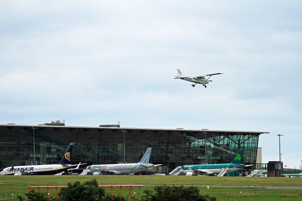 Cessna 172, EI-EAM, from Atlantic Flight Training landing at Cork airport with Ryanair, AllItalia and Aer Lingus parked at the terminal